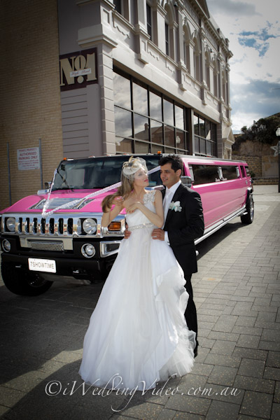 bridal couple in front of their limo